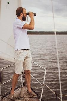 Uomo barbuto che guarda binoculare sulla barca a vela
