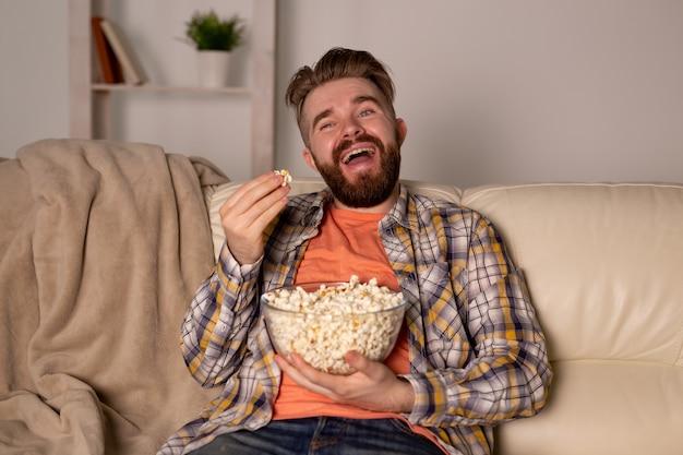 Uomo barbuto che guarda film o giochi sportivi tv mangiare popcorn in casa di notte. concetto di cinema, campionato e tempo libero.