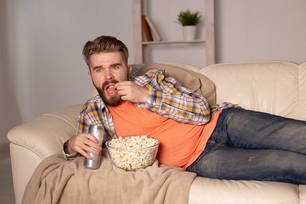 Uomo barbuto che guarda film o giochi sportivi tv mangiare popcorn in casa di notte. cinema, campionato