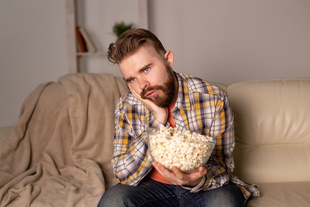 Uomo barbuto che guarda film o giochi sportivi in tv mangiando popcorn in casa durante il campionato di cinema notturno e