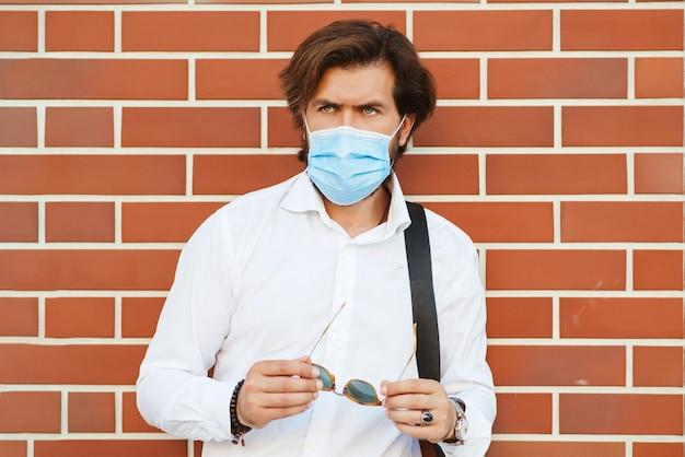 Uomo barbuto che indossa la maschera per il viso all'aperto. uomo barbuto alla moda in camicia bianca con borsa.