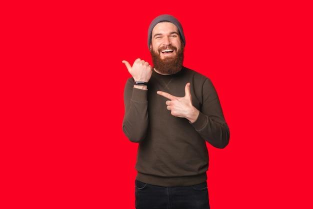 L'uomo barbuto che indossa un cappello e un maglione caldi sta indicando il suo orologio da polso.