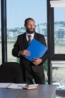 Uomo barbuto che indossa camicia bianca cravatta e abito nero che tiene la cartella blu con i documenti che ci guardano. riunione di lavoro mattutina in ufficio. uomo d'affari con documenti e cartelle.