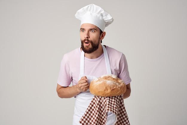 Uomo barbuto in grembiule bianco panettiere che tiene il pane in mano. foto di alta qualità