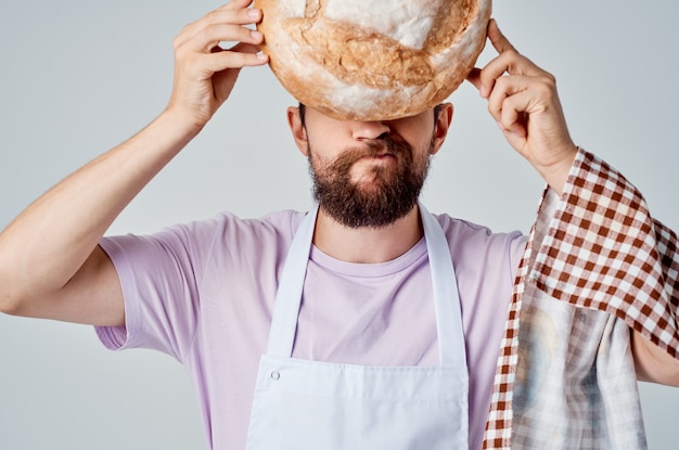 Uomo barbuto in grembiule bianco che cucina cibo