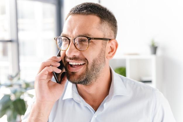 Uomo barbuto in camicia bianca sorridente e parlando su smartphone nero di affari, mentre si lavora in ufficio