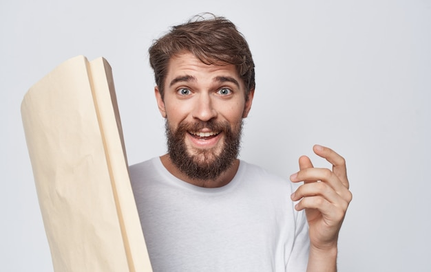 Uomo barbuto in t-shirt bianca pacchetto shopping artigianale