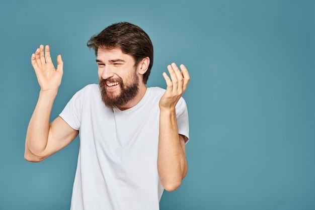 Un uomo barbuto in una maglietta bianca gesticola con le sue mani emozioni blu.
