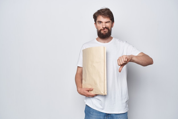 Uomo barbuto nel pacchetto della spesa borsa kraft t-shirt bianca. foto di alta qualità