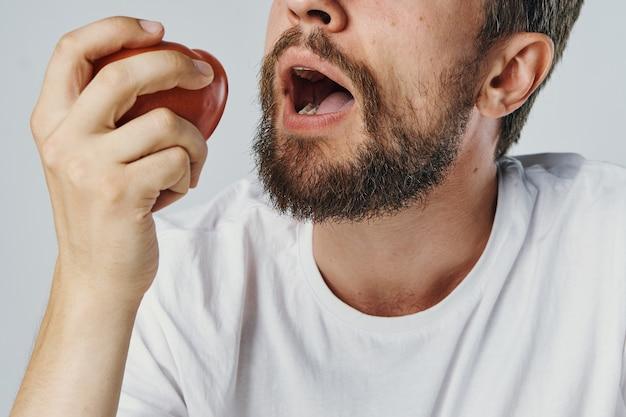 Uomo barbuto in t-shirt bianca verdure dieta salute vegetariana