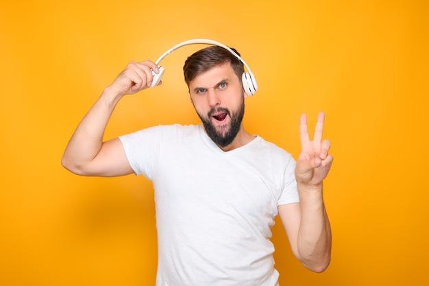 Un uomo barbuto con una maglietta bianca, in piedi su uno sfondo giallo, ascolta musica con le cuffie.