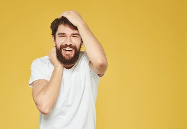 L'uomo barbuto in una maglietta bianca fa gesti di rabbia in primo piano