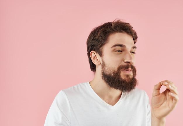 Uomo barbuto in uno studio di gesti delle mani di una maglietta bianca