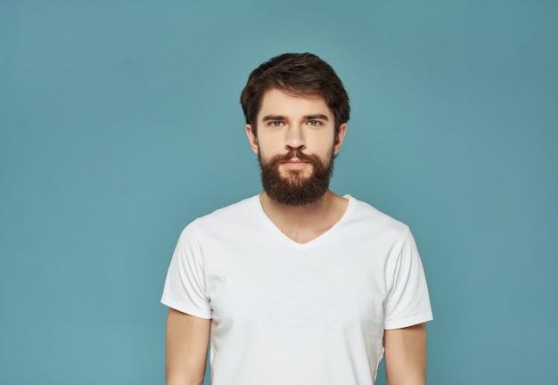 L'uomo barbuto con una maglietta bianca ha irritato il primo piano dell'espressione facciale
