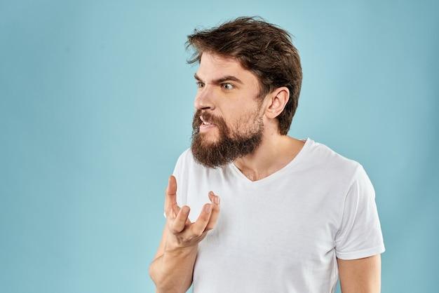 Uomo barbuto in maglietta bianca in posa contro il muro blu