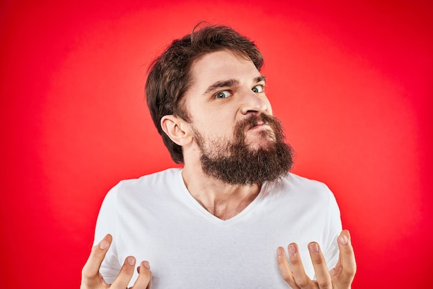 Uomo barbuto in maglietta bianca in posa contro il muro rosso