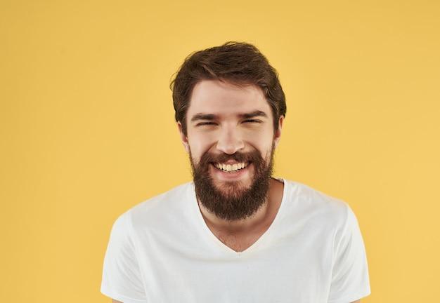 Uomo barbuto in maglietta bianca in posa divertente in studio