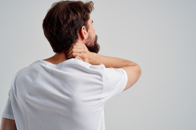 L'uomo barbuto con una maglietta bianca stressa la medicina per il dolore al collo isolato sullo sfondo