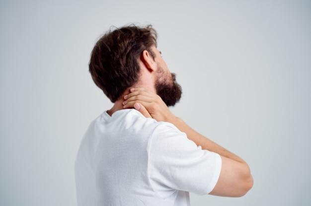 L'uomo barbuto con una maglietta bianca stressa il dolore della medicina sullo sfondo chiaro del collo