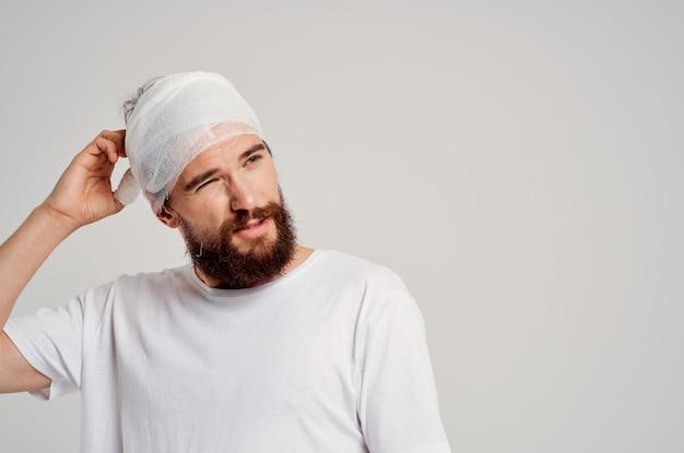 L'uomo barbuto in una maglietta bianca ha isolato la diagnosi di salute del trauma sullo sfondo