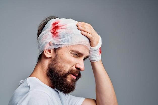 Uomo barbuto in uno sfondo chiaro di diagnosi di salute trauma tshirt bianca