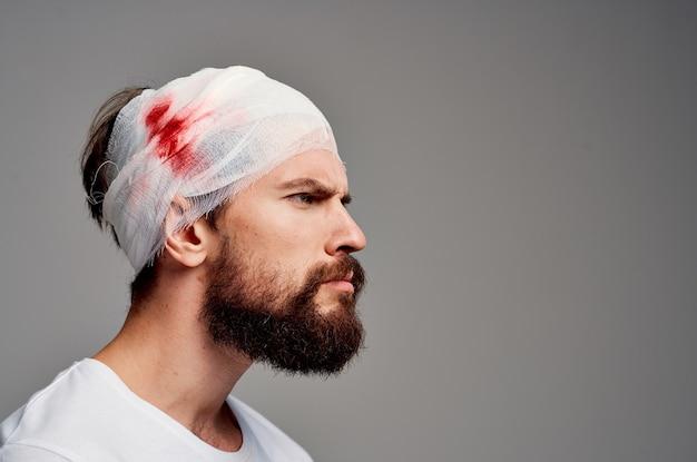 Uomo barbuto in una maglietta bianca trattamento di diagnosi di trauma di salute