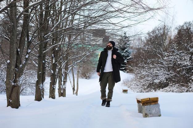 Uomo barbuto nei boschi invernali. attraente giovane felice con la barba a piedi nel parco.