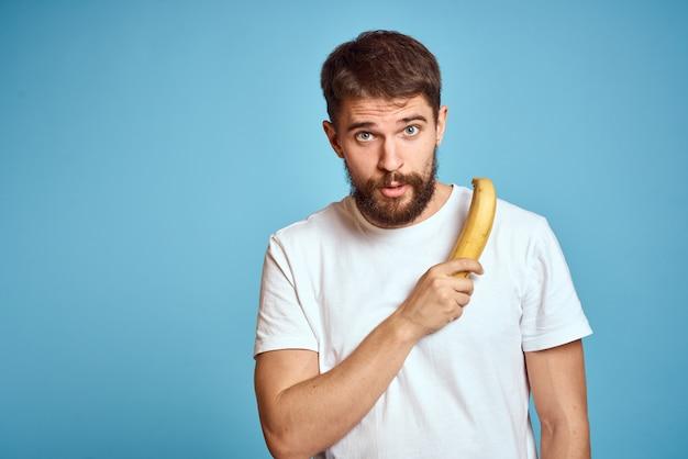 Uomo barbuto con banana in mano sull'azzurro