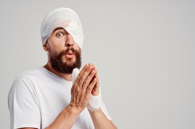 Uomo barbuto con la testa fasciata e uno sfondo chiaro di sangue negli occhi