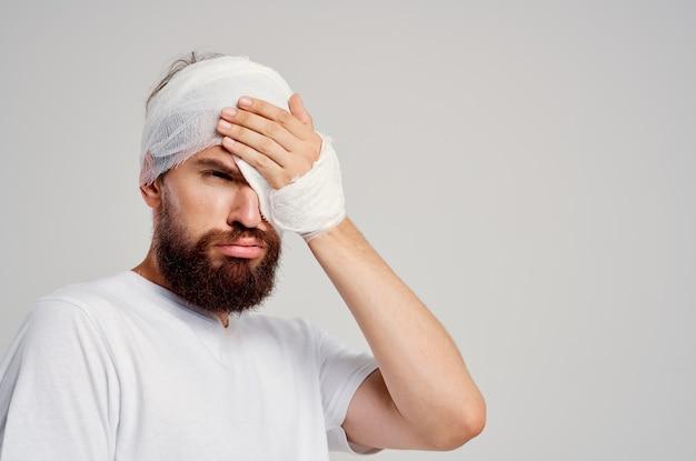 Uomo barbuto con la testa fasciata e l'ospedalizzazione degli occhi medicina ospedaliera. foto di alta qualità