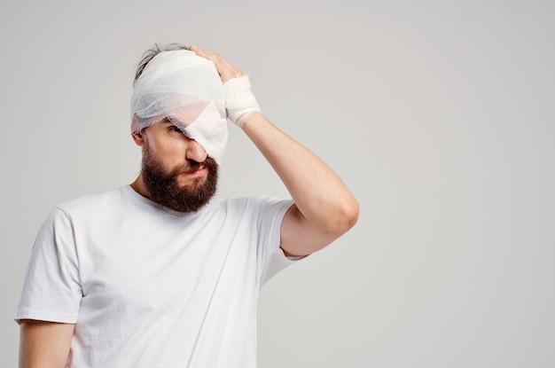 Uomo barbuto con la testa fasciata e lo sfondo chiaro di ospedalizzazione degli occhi