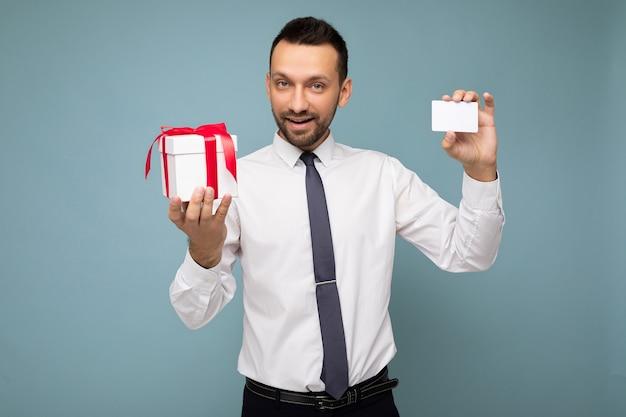 Uomo barbuto con la barba isolato sul muro blu che indossa una camicia bianca e cravatta che tiene scatola regalo bianca con nastro rosso e carta di credito.