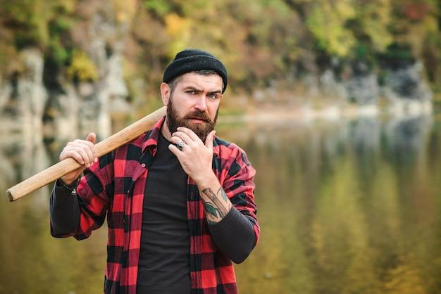 Uomo barbuto con barba e baffi dal fiume vicino alla foresta