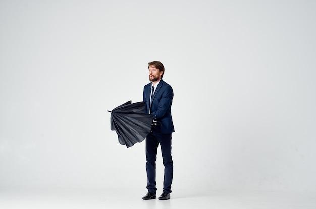 Uomo barbuto con un ombrello nero e in un vestito su uno sfondo chiaro in piena crescita. foto di alta qualità