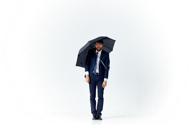 Uomo barbuto con un ombrello nero e in un vestito su uno sfondo chiaro in piena crescita