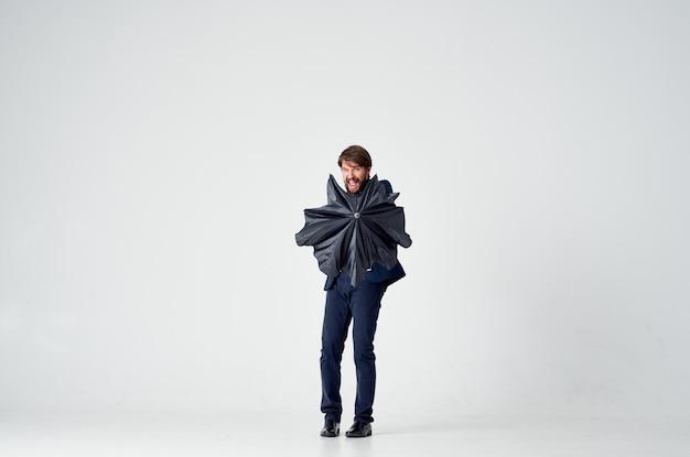 Uomo barbuto con un ombrello nero e in un vestito su uno spazio luminoso in piena crescita