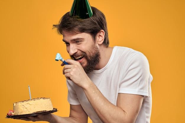 Uomo barbuto con una torta e in un berretto che celebra il suo compleanno