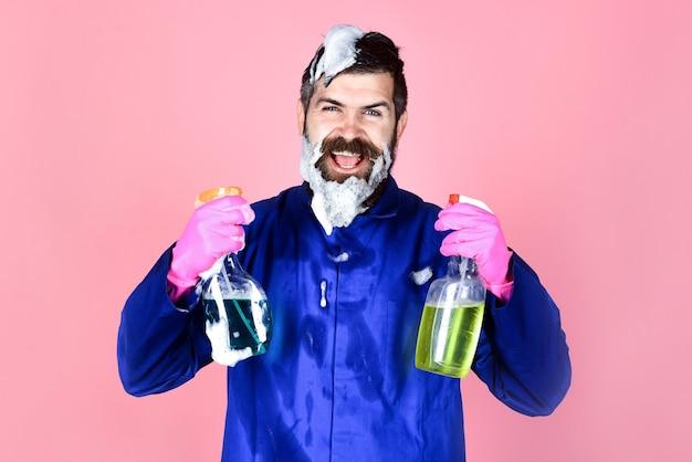 Uomo barbuto con attrezzature per la pulizia. concetto di pulizia. ritratto di uomo barbuto felice con spray detergente. uomo barbuto in uniforme da lavoro. pubblicità di pulizia. pulitori.
