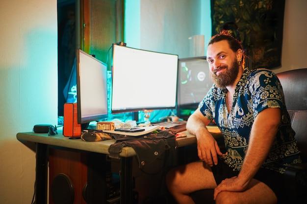 Uomo barbuto con computer e 2 schermi che guarda e sorride alla telecamera