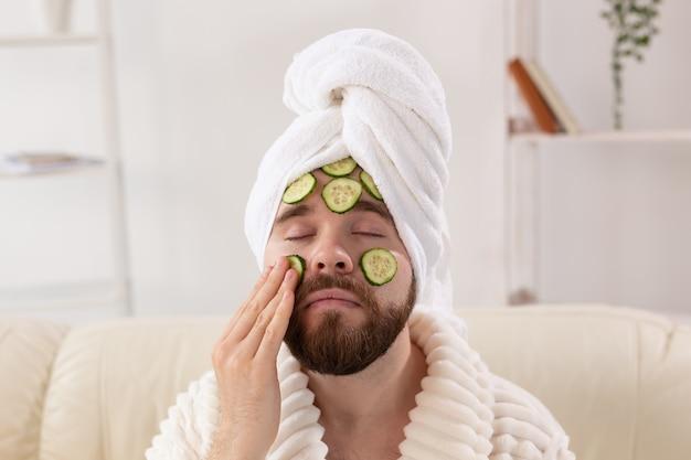 Uomo barbuto con una maschera cosmetica sul viso a base di fette di cetriolo