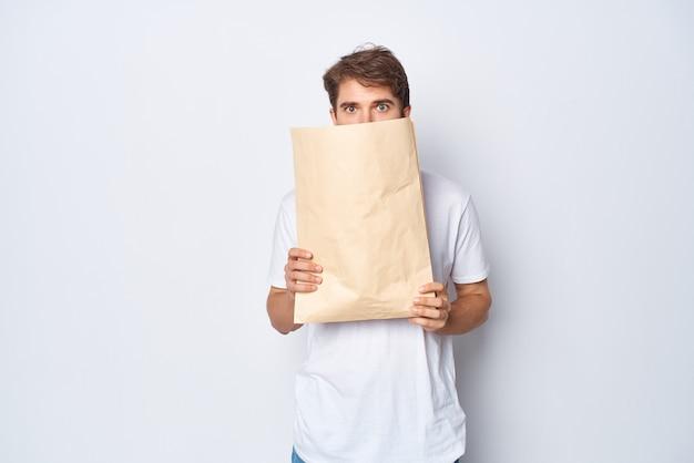 Uomo barbuto con pacchetto artigianale nelle mani che acquistano emozioni sfondo chiaro