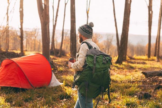 Uomo barbuto con una tazza di caffè, indossando lo zaino vicino alla tenda rossa alla foresta all'aperto
