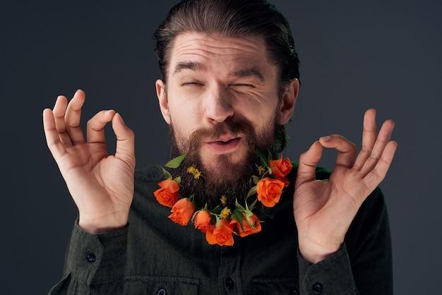 Uomo barbuto con fiori decorazione romanticismo attraente primo piano sguardo. foto di alta qualità