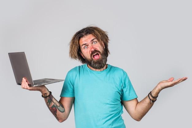 Uomo barbuto con laptop. dispositivo digitale. uomo serio di affari con il computer. lavoro da casa.