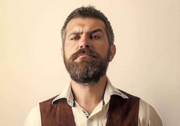 Uomo barbuto con barba lunga sul viso serio in camicia isolato.