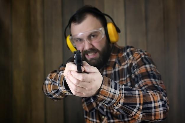 Uomo barbuto con occhiali protettivi e addestramento all'orecchio nel tiro con la pistola