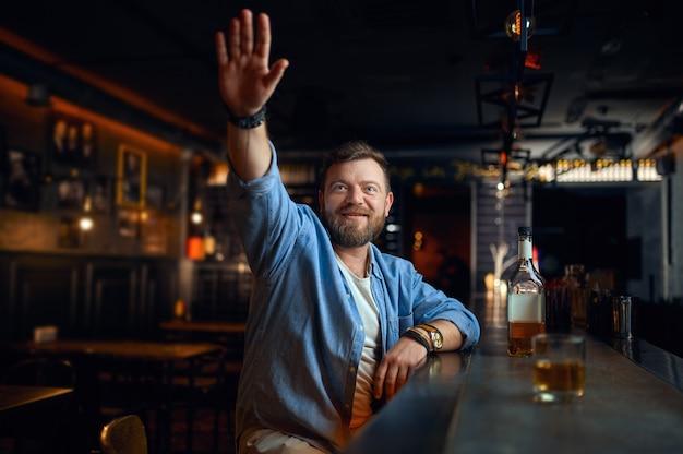 Uomo barbuto con la mano alzata seduto al bancone del bar. una persona di sesso maschile che riposa in un pub, emozioni umane, attività ricreative, vita notturna