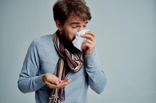 Uomo barbuto con una sciarpa intorno al collo problemi di salute influenza sfondo chiaro