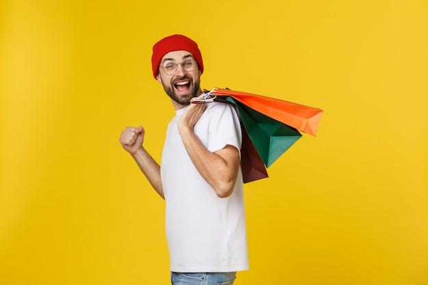 Uomo barbuto con i sacchetti della spesa con la sensibilità felice isolata su giallo