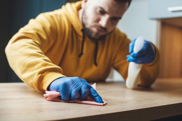 L'uomo barbuto con uno spray speciale sta pulendo la casa e disinfettandola durante la situazione di pandemia